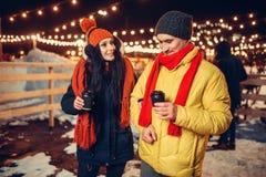 Sera di inverno, passeggiate delle coppie con caffè all'aperto fotografia stock libera da diritti