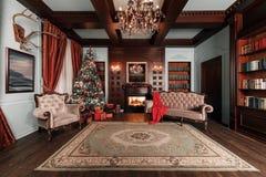 Sera di natale appartamenti classici con un camino bianco, un albero decorato, un sofà, le grandi finestre e un candeliere immagini stock