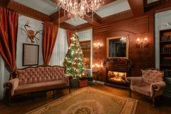 Sera di natale Regali all'albero di Natale appartamenti classici con un camino Stanza con gli scaffali dei libri fotografie stock libere da diritti