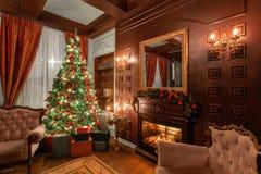 Sera di natale Regali all'albero di Natale appartamenti classici con un camino Stanza con gli scaffali dei libri fotografia stock