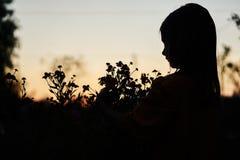 Sera di notte della bambina del fiore della siluetta immagine stock libera da diritti