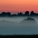 Sera e tramonto nebbiosi Immagini Stock