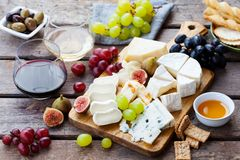 Sera i owoc asortyment na tnącej desce z czerwienią, biały wino na drewnianym tle zdjęcie royalty free