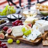 Sera i owoc asortyment na tnącej desce z czerwienią, biały wino na drewnianym tle kosmos kopii obrazy stock