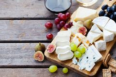 Sera i owoc asortyment na tnącej desce z czerwienią, biały wino na drewnianym tle kosmos kopii fotografia stock