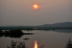 Sera nebbiosa sul lago con un pescatore in una barca con la riflessione della foresta e del sole Immagini Stock Libere da Diritti