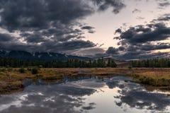 Sera nuvolosa di riflessioni del fiume delle montagne Immagine Stock