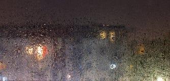 Sera piovosa e la vista del vetro coperto di pioggia attraverso cui potete vedere un caseggiato sfocato fotografie stock libere da diritti