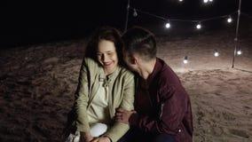 Sera romantica alla spiaggia, la ragazza ed il tipo felici si siedono sulla sabbia su un fondo della decorazione con le lampade l