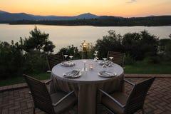 Sera romantica di estate nel ristorante - la tavola è servito per quattro persone con una vista del tramonto alla maratona del la fotografia stock
