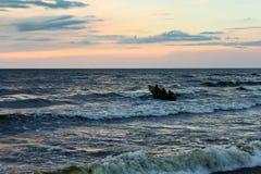 Sera sul mare, buio, una barca, pochi uomini tre Immagine Stock Libera da Diritti
