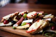 Serba talerz dla czerwonego wina: Ñ  heese, bekonowy, oliwki, arugula, wiśnia, bruschetta fotografia stock