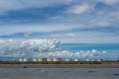 Serbatoi dell'olio in una fila sotto cielo blu, grande carro armato industriale bianco f immagine stock