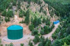 Serbatoio chimico della grande acqua industriale verde in foresta delle colline della montagna Fotografia Stock