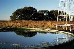 Serbatoio delle azione & del mulino a vento su un ranch nel Texas Fotografia Stock