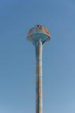 Serbatoio di acqua blu arrugginito della torre su fondo blu fotografia stock libera da diritti