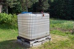 Serbatoio di acqua di plastica quadrato nel giardino baril del ricuperatore dell'acqua piovana Fotografia Stock Libera da Diritti