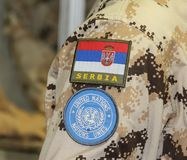 Serbia; Belgrade; June 6, 2017; Serbian flag and UN logo on yell. Ow camouflage uniform; The 8th International Armament Fair from 27th to 30th June royalty free stock images