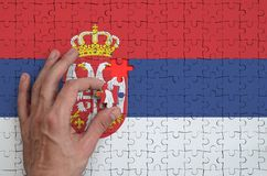 Serbia flag is depicted on a puzzle, which the man`s hand completes to fold.  stock illustration