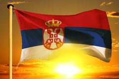 Serbia flag weaving on the beautiful orange sunset with clouds background. Serbia flag weaving on the beautiful orange sunset background stock photos