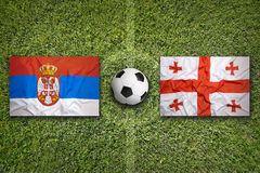 Serbia vs. Georgia flags on soccer field Royalty Free Stock Image