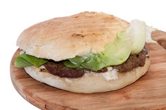 Serbian burger with lettuce served on a wooden board Stock Photography