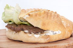 Serbian burger with lettuce served on a wooden board Stock Image