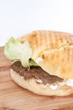 Serbian burger with lettuce served on a wooden board Royalty Free Stock Images