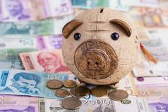 Serbian dinars and piggy bank. Wooden piggy bank looking at camera on top of pile of Serbian dinars royalty free stock image