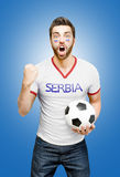 Serbian fan holding a soccer ball celebrates on blue background Stock Images