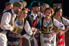 Serbian folk dancers perform in a show. ROMANIA, TIMISOARA - JULY 7, 2016: Young Serbian dancers in traditional costume, perform folk dance during International royalty free stock photography