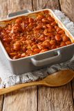 Serbian food: prebranac baked beans with onion close-up in baking dish. vertical stock photos