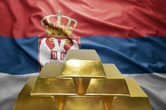 Serbian gold reserves. Shining golden bullions on the serbian flag background stock image