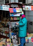 Serbian woman attends to outdoor magazine books & vinyl stall Belgrade Serbia Royalty Free Stock Photo