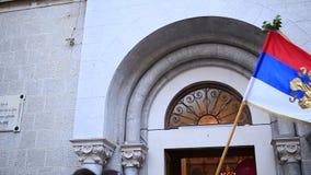 Serbien flagga som framme vinkar av kyrkan i Kotor stock video