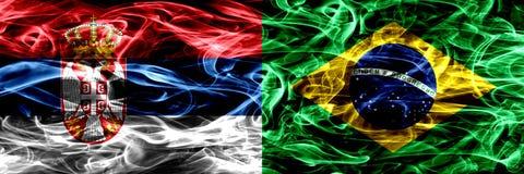 Serbien gegen Brasilien, brasilianische Rauchflaggen nebeneinander gesetzt Thi lizenzfreie stockbilder