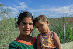 Serbien im Oktober 2015: Eine junge syrische Frau, die ein Kind auf der Grenze mit der Europäischen Gemeinschaft hält Lizenzfreie Stockfotografie