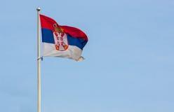 Serbische Flagge mit blauem Himmel Lizenzfreie Stockfotos