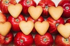 Serc kształtni ciastka na czerwonych jabłkach Odgórny widok Zdjęcia Royalty Free