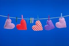Serca wiesza na clothesline z clothespins, błękitny backgroun Obrazy Stock