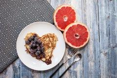 Serce bliny z czernicami na białym talerzu drewniany tło z grapefruitowym Romantyczny lub zdrowy śniadanie obraz stock