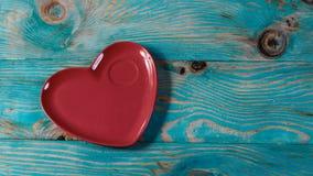 Serce czerwieni formularzowy talerz Odizolowywający na błękitnym drewnianym tle Walentynki ` s dnia menu Uwalnia przestrzeń dla t obrazy royalty free