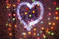 Serce jarzy się przez mokrego szkła wśród kolorowego Bokeh Fotografia Stock
