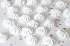 Serce kropi i małe świeże piec bezy na bielu ukazują się zdjęcie stock