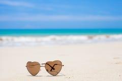Serce kształtni okulary przeciwsłoneczni kłama na tropikalnym piasku fotografia stock