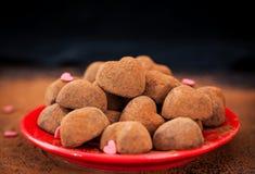 Serce kształtować czekoladowe trufle na czerwień talerzu Obrazy Stock