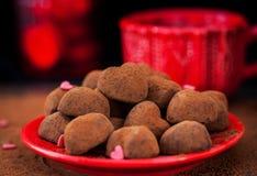 Serce kształtować czekoladowe trufle na czerwień talerzu Fotografia Royalty Free