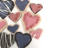 Serce Kształtował czekoladowych i waniliowych ciastka z różowym lodowaceniem zdjęcie royalty free