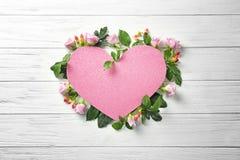 Serce kształtował prześcieradło papier z pięknymi kwiatami na białym drewnianym tle obrazy royalty free