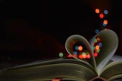 Serce kształtował strony w książce z kolorowymi światłami zdjęcie stock